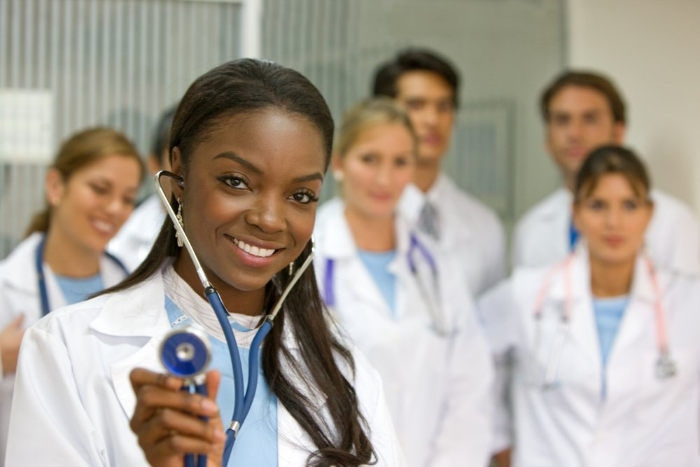 female doctor holding a stethoscope with her team behind